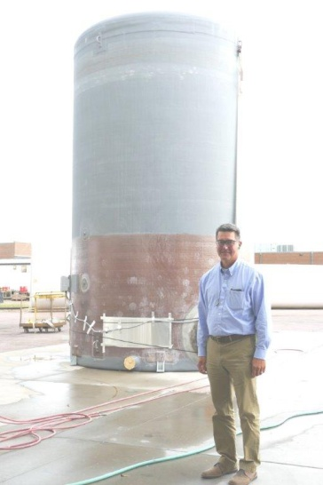 Design Tanks CEO Marty Comes stands in front of one of the company's fiberglass tanks.